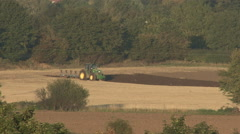 Tractor tows plough / plow in evening sunshine. - stock footage