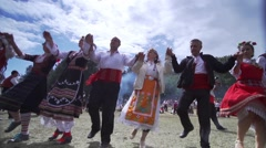Men and women play Bulgarian folk dances of mountain meadow in slow motion Stock Footage