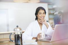 Portrait smiling woman in bathrobe drinking coffee at laptop - stock photo