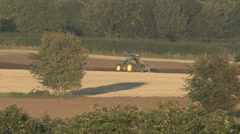Stock Video Footage of Tractor tows plough / plow in evening sunshine.