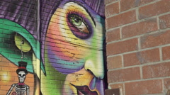 Graffiti art in the city. Beautiful and colorful girl. Slider Shot. 4K UHD. Stock Footage