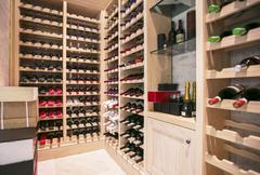 Wine bottles organized on racks in wine cellar Stock Photos
