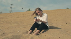 Beautiful girl sitting on the sand against the backdrop of the cable car with Stock Footage