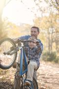 Father teaching son how to do a wheelie in woods Stock Photos