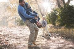 Playful father lifting son upside-down on path in woods Stock Photos