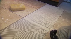 Mason attaching tiles on floor - stock footage