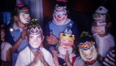 2611 - children wear mask during birthday party - vintage film home movie - stock footage
