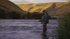 Man fly fishing in beautiful river at sunrise, rack focus - stock footage