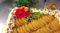 Stock Video Footage of Decorating a cake with edible flowers, at a restaurant bakery