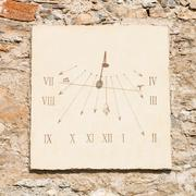 vertical sundial made of  carved stone's slab  and  iron rod - stock photo