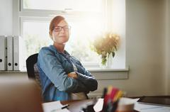 Confident Office Woman Sitting at her Desk - stock photo