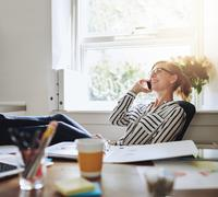 Happy Businesswoman at her Desk Talking on Phone - stock photo