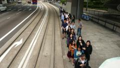 Passengers queue up to tram stop, walk towards in line, tramway departs away Stock Footage