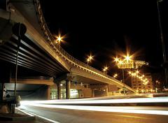Car headlights traces under road bridge in night city - stock photo