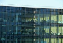 Panoramic windows of the office building with work places inside - stock photo