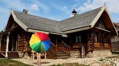 Girl twirling colorful umbrellas beside a village house from a bar Stock Footage