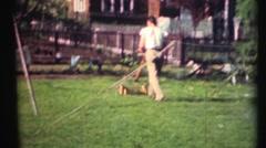 1948  ,Mom using push lawn mower Stock Footage
