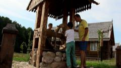 Man with children are bucket of water from the well in the Russian village Stock Footage