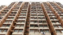 Heavily occupied tall apartments building, high angle view from street level Stock Footage