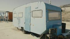 Rickety old vintage abandoned caravan/trailer in a deserted camp/area - stock footage