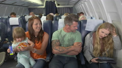 Male passenger on plan hits on young pretty female passenger Stock Footage