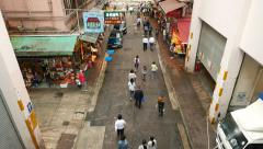 People walk along Wan Chai road, street market stalls, garage doors Stock Footage