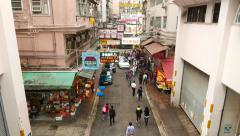 White car slowly drive through Wan Chai road, people walk around Stock Footage