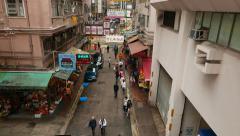 Citizens walk along Wan Chai road at Bowrington Market area, slide shot above Stock Footage