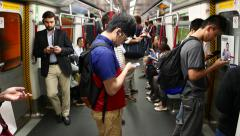 Young man stand in metro carriage, look to smart phone listen headphones - stock footage