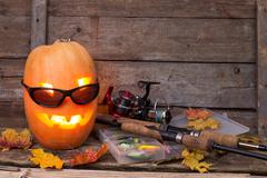 Halloween pumpkin in eyeglass with fishing tackles Stock Photos