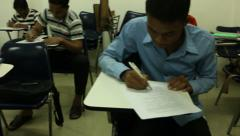 Asian students taking a midterm exam with camera panning to reveal various st Stock Footage