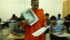 Asian students taking a midterm exam, featuring a young monk leaving his exam Stock Footage