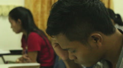 Asian students taking a midterm exam with camera moving through rows to revea Stock Footage