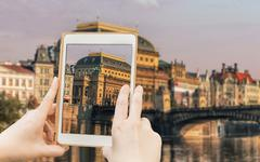Stock Photo of Taking shot of famous Prague historical sight with a tablet.