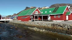 Greenland small town Qaqortoq 091 wooden red houses with green roofs at creek Stock Footage