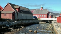 Greenland small town Qaqortoq 090 stony creek and red wooden church Stock Footage