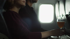 Young woman is drinking a cocktail on an airplane and man is listening to music Stock Footage