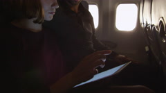 Couple are sitting together on a plane and using tablet Stock Footage