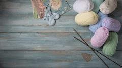 Needles, Assorted Yarn, and Booties On Faded Blue Wooden Background - stock photo