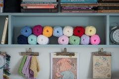 Yarn and Knitting Books Organized on Shelf Over Clipboards Stock Photos