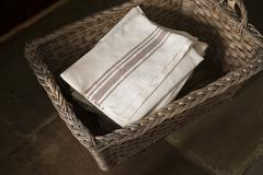 Pile of Striped Table Napkins in a Rectangular Woven Basket - stock photo