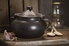 Covered black tureen alongside cloves of garlic and a pair of wooden spoons o Stock Photos