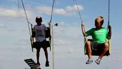 Two boys swinging on a swing, a swing with an iron chain Stock Footage