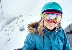 Portrait of young woman snowboarder in sunglass mask, rises to the top in the - stock photo