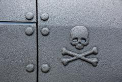 Warning sign skull and crossbones on a black background - stock photo