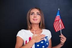 Patriotic woman holding USA flag and looking up - stock photo