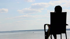 Silhouette woman sitting on the beach wears glasses and looks at river Stock Footage