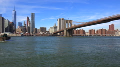 A barge and tugboat moves up New York's East River and crosses under the Stock Footage