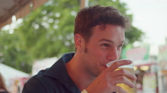 A young man drinking a beverage and talking to someone across from him Stock Footage
