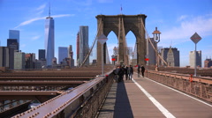 Pedestrians cross the Brooklyn Bridge with Manhattan and the Freedom Tower in Stock Footage